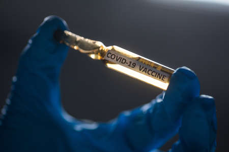 Conceptual image of a nurse holding a recipient with the coronavirus COVID-19 vaccine. Stok Fotoğraf