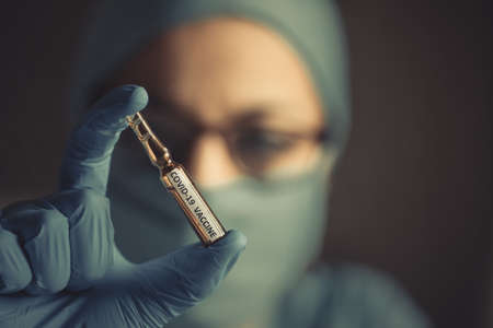 Conceptual image of a nurse holding a recipient with the coronavirus COVID-19 vaccine. Фото со стока