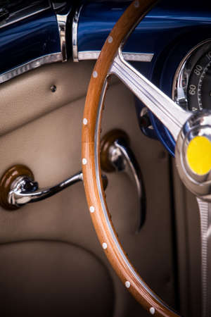 Color close up of the wooden steering wheel of an old classic car.