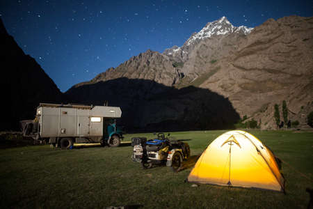 A motorhome, a sidecar motorcycle and a tent, camping at night in the mountains. 写真素材