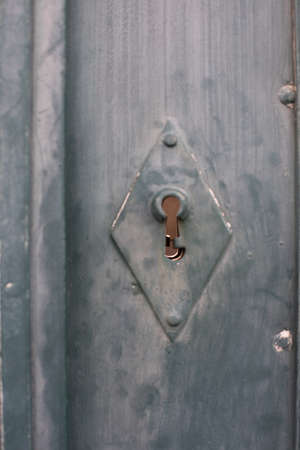 Close up shot of a keyhole on a wooden door.
