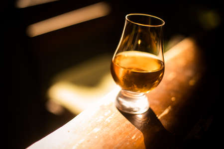 Color close up shot a Glencairn whisky glass on a wooden table, with shallow depth of field.