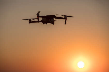 Color image of a drone flying at sunrise. 版權商用圖片