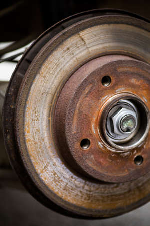 Close up shot of a car worn and rusty brake disk.