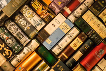 Bucharest, Romania - December 2, 2020: Illustrative editorial image of many whisky bottle packaging arranged on a wall in Bucharest, Romania.