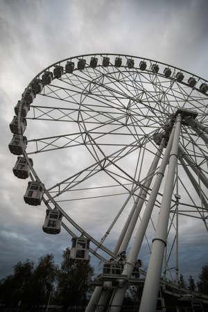 Image of a big ferris wheel against a cloudy sky.