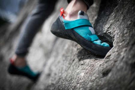 Close up shot o a person climbing while wearing rock climbing shoes.