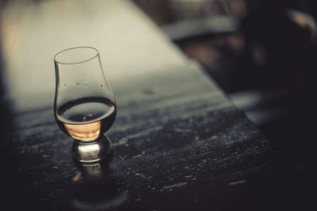 Color close up shot of a Glencairn whisky glass on a wooden table, with shallow depth of field.