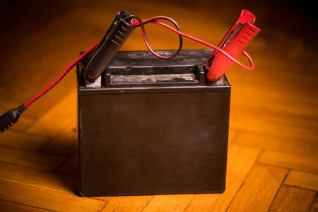 Color close up shot of a motorcycle lead battery being charged with cables.