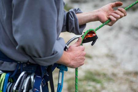 Close up shot of a man's hands operating a rock climbing belaying device. Standard-Bild