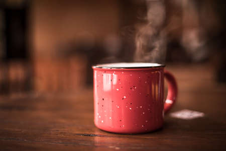 Close up shot of a steamy red metal mug on a wooden table.