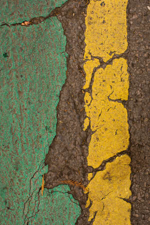 A patch of weathered paint, green and yellow.
