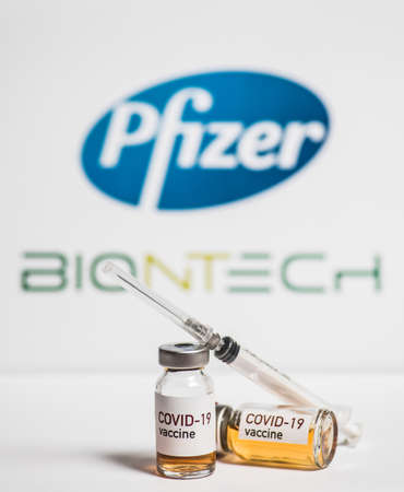 Bucharest, ROMANIA - March 15, 2021: Illustrative editorial concept image with a dose of the new Coronavirus COVID-19 vaccine, with the Pfizer and Biontech logos in the background.
