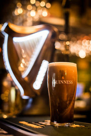 Bucharest, Romania - February 25, 2021: Illustrative editorial close up image of a pint of Guinness beer on a pub's counter.