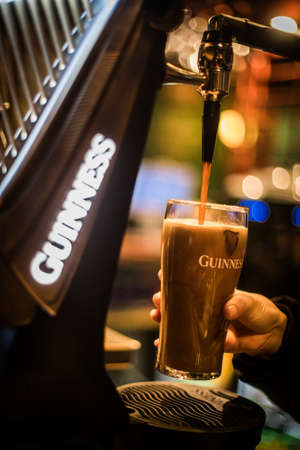 Bucharest, Romania - February 25, 2021: Illustrative editorial close up image of a bartender pouring a pint of Guinness beer in a pub.