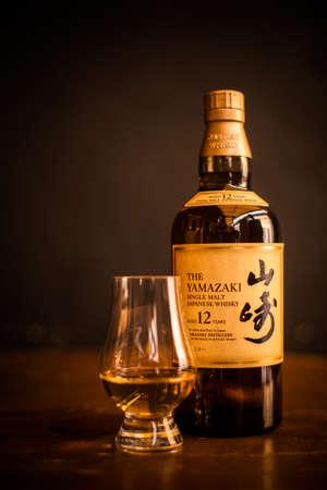 Bucharest, Romania - February 25, 2021: Illustrative editorial image of a Yamazaki single malt Japanese whisky bottle and a Glencairn whisky glass in Bucharest, Romania.