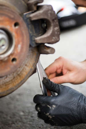 Close up shot of a mechanic working at a car worn and rusty brake disk and caliper.