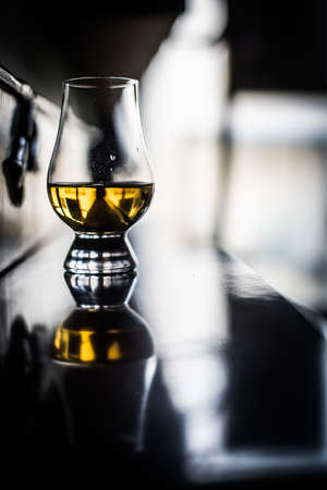 Color close up shot a hand holding a Glencairn whisky glass on a wooden table, with shallow depth of field. Standard-Bild