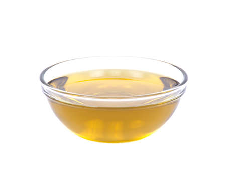 Extra virgin oil in bowl separated on white background Фото со стока