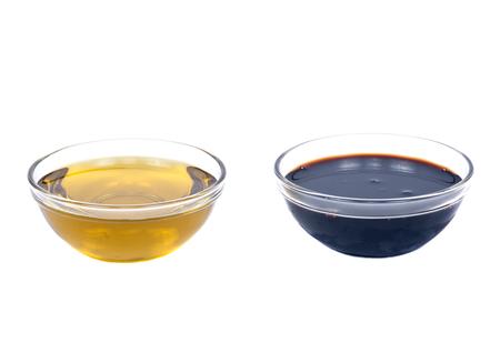 Aceite de oliva virgen extra y vinagre balsámico en un tazón separados en el fondo blanco Foto de archivo - 53749361