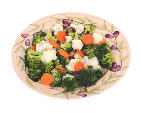 Steam cooked vegetables on plate separated on white background