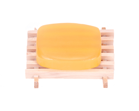 Goat milk soap on natural wood dish separated on white background