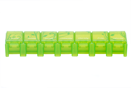 pillbox: Green weekly pill organizer separated on white background Stock Photo