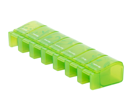 Green weekly pill organizer separated on white background Stock Photo
