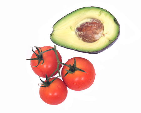 Cut in half avocado and ripe organic tomatoes with drops of water separated on white background