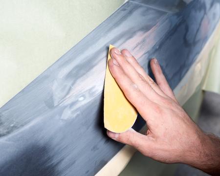 repaint: Worker hand sanding filler preparing for repaint Stock Photo