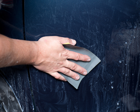 buffing: Worker hand sanding auto body preparing for buffing