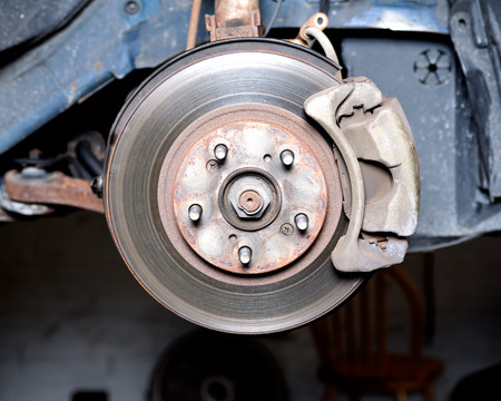 brake caliper: Front disc brake caliper, bracket, rotor of a car after accident on hydraulic lift