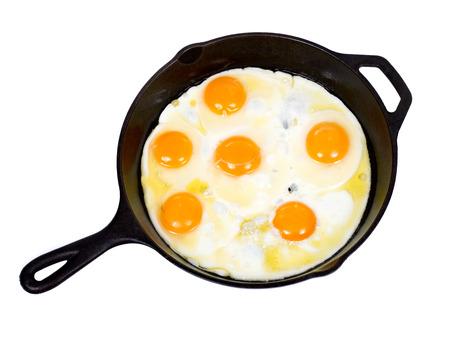 amish: Fried eggs on cast iron skillet isolated on white background Stock Photo