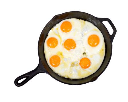 amish: Fried eggs on cast iron skillet with salt isolated on white background Stock Photo