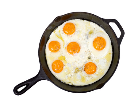 amish: Fried eggs on cast iron skillet with salt and pepper isolated on white background