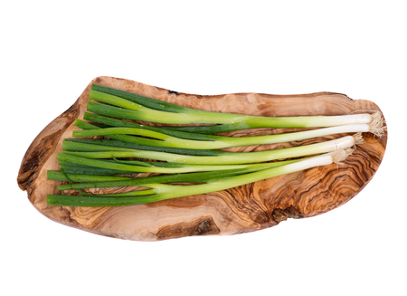 Organic green onion on olive wood cutting board isolated on white background