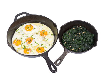 amish: Fried eggs and sauteed spinach on cast iron skillet isolated on white background
