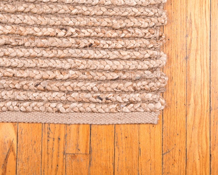 Jute pile hand woven beige area rug on old hardwood floor Imagens
