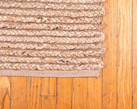 Jute stapel met de hand geweven beige tapijt op oude houten vloer Stockfoto