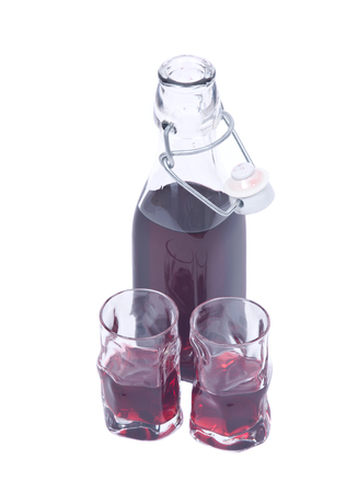 liqueur bottle: Homemade raspberry liqueur in clear glass bottle with swing top and shot glass isolated on white background