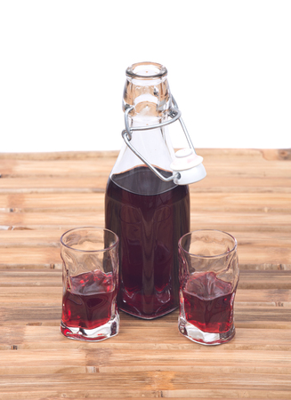 liqueur bottle: Homemade raspberry liqueur in clear glass bottle with swing top and shot glass on bamboo table