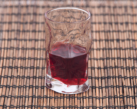 Homemade raspberry liqueur in shot glass isolated on bamboo placemat