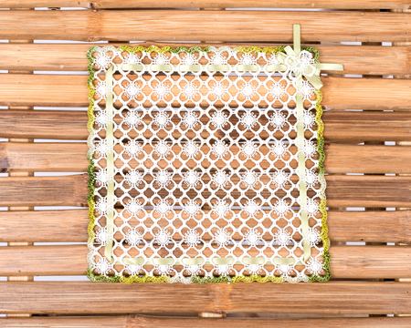 lace doily: Colorful fabric lace doily on natural bamboo table Stock Photo
