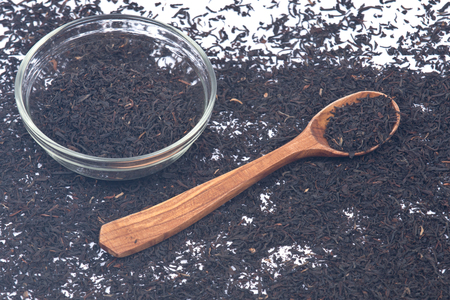 assam tea: Certified organic camellia assam tea with wooden spoon and bowl