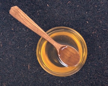 assam tea: Organic amish farm pure honey in bowl and camellia assam tea with wooden spoon