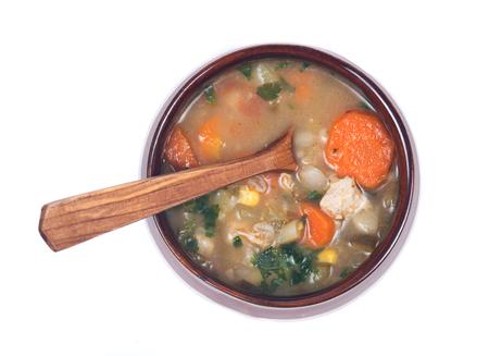 Kip, gerst en groentesoep in keramische kom met houten lepel geïsoleerd op een witte achtergrond