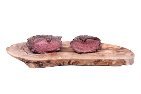 grass cutting: Grass fed juicy corn roast beef on olive wood cutting board isolated on white background