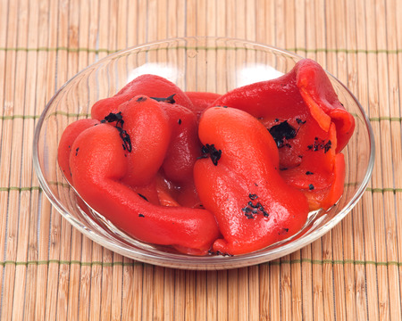 Fire roasted red peppers in bowl on bamboo placemat Stock Photo