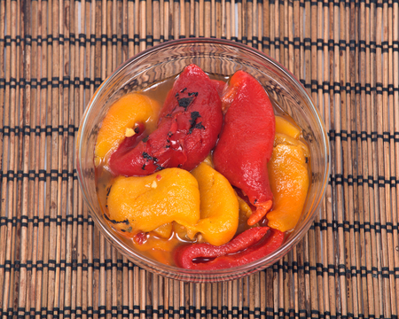 Fire roasted yellow and red peppers in bowl on bamboo placemat