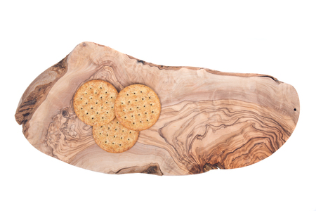 Wheat crackers on olive wood cutting board isolated on white background